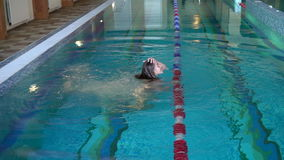 The girl dives in the pool and smiles. Indoor swimming pool stock video footage