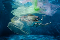 Girl dives into the tissue. Stock Photography