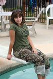 Girl On Diving Board. Girl sitting on diving board wearing camouflage Royalty Free Stock Images