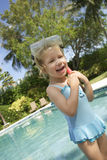 Girl With Diving Mask And Snorkel At Poolside. Happy cute little girl with diving mask and snorkel at poolside Stock Photo