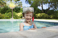 Girl With Diving Mask And Snorkel In Swimming Pool. Portrait of cute little girl with diving mask and snorkel in swimming pool Stock Photo
