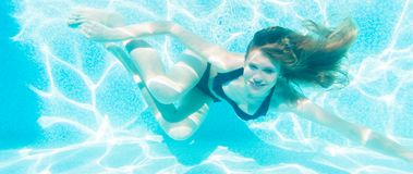 Girl diving underwater in swimming pool. Happy girl diving underwater in swimming pool stock image