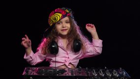 Girl dj in bright cap playing on turntable. Slow motion. Girl dj in bright cap playing on turntable, on neck of child wearing headphones, wearing stylish pink stock footage