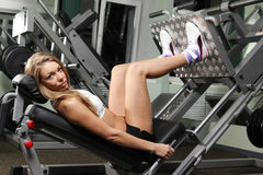 Girl do exercise for legs. In fitness gym looking at the camera Stock Photos
