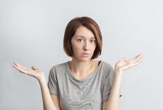 Girl do not agry with something or do not understand. Girl puzzled shrugs, misunderstanding and disagreeing Stock Photos