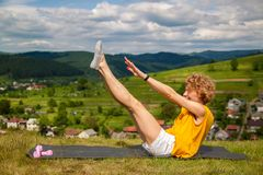 Girl do yoga outdoors nature training on the mountain. royalty free stock images