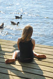 Girl on dock with duck Stock Photo