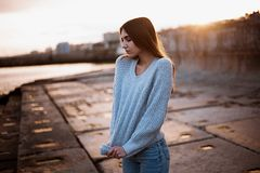 Girl in a sweater near the sea. Girl on the dock in a sweater near the sea Royalty Free Stock Images