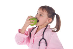Girl, a doctor, the child, apple Stock Images
