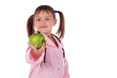 Girl, a doctor, the child, apple. Children dressed as doctors, nurses Stock Image