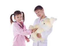 Girl, a doctor, the child, rabbit toy. Children dressed as doctors, nurses Royalty Free Stock Images