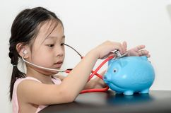 Girl doctor cure with piggy bank,. Money concept Stock Images