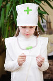 Girl at the doctor's clothes and stethoscope on his neck looking Royalty Free Stock Photos