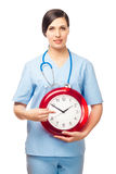 The girl-doctor shows a finger on an alarm clock. Royalty Free Stock Image