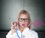 Girl with doctor uniform. Caucasian young girl playing doctor on background royalty free stock photo