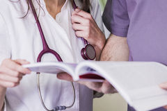 Girl Doctor in a white coat with a stethoscope and male doctor with book.  Stock Photography