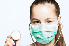 Girl in a doctors mask holding a stethoscope - medical concept Royalty Free Stock Images