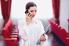girl with documents speaks by phone stock images