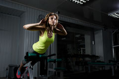 Girl does a body lift in the gym. Sporty young girl doing body lifting on a fitness machine in the gym Royalty Free Stock Photography