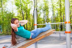 Girl does curls up on the wooden board outside Stock Photography