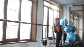 Girl does deadlift with straight legs and a barbell. Stand straight with feet shoulder width slightly wider than shoulder width, grab a barbell. Weights should stock video