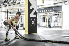 Girl does exercise with fitness rope in gym Stock Images