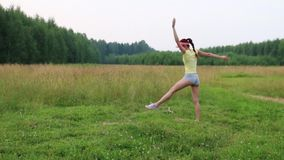 Girl does exercise somersault on meadow at summer evening stock video