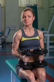 The girl does exercises with dumbbells Stock Photography