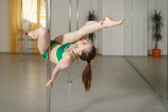 Girl does exercises on a pylon in the gym Stock Photos