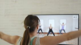 The girl does exercises while watching a program on TV at home. A young woman in sportswear, athletic build, plays