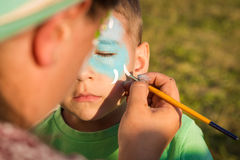 Girl does greasepaint on the child's face Royalty Free Stock Photos