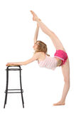 Girl does gymnastics, keeping for stool Royalty Free Stock Photos