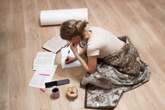 Girl does her homework. A blonde girl does her homework on the floor. There are copybooks, books, a cup of tea and cookies Royalty Free Stock Image