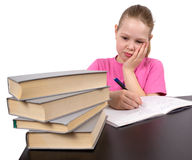 The girl does homework. On desktop with books Royalty Free Stock Image