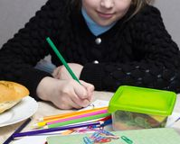 The girl does the lessons, on the table lies a sandwich, fruit, nuts, textbooks, pencils, nosh stock image