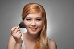 Girl does a make-up. Young beautiful girl does make-up. Close up Stock Photos