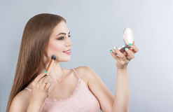 The girl does make-up looking in a mirror Stock Photo