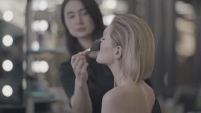 Girl does makeup by the mirror.  stock footage