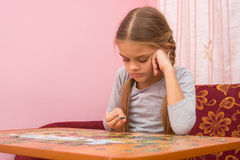Girl does not know where to put the next puzzle element Stock Photos