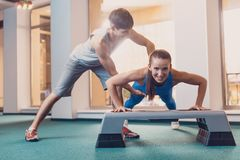 Girl does push ups from the bench with a trainer. A happy girl performs a physical exercise on the strength of the hands under the control of a trainer. Push royalty free stock photo