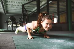 The girl does push-ups from the floor in the gym. stock photo