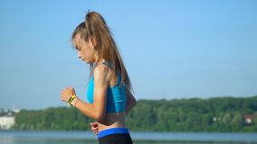 The girl does sports exercises and workout on lake background. Girl is swept away before the jog