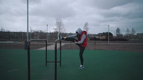 Girl does warm-up on sports ground. stock video
