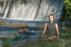 Girl does yoga in the background of a waterfall stock photography