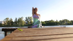 Girl does yoga on wooden bridge at lake at sunset. stock video footage