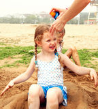 A Girl Doesn't Like Being Sprayed with Sunscreen. A Little Girl Doesn't Like Mommy Spraying Her with Sunscreen at the Beach Stock Photography