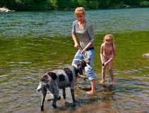 Girl and Dog 1. Two young girls play with dog at river. Summer, sunny day. Russian Far East, Primorye Stock Image