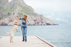 Girl with dog. Beautiful girl playing with her dog on berth near sea Stock Images