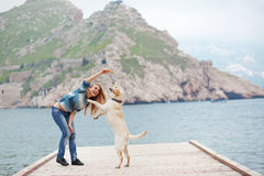 Girl with dog. Beautiful girl playing with her dog on berth near sea Royalty Free Stock Photo
