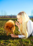 Girl with a dog. Pretty blond girl having a walk in the park with her dog Royalty Free Stock Photos